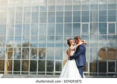Lovely wedding couple embrance and stands near modern glass building on background. Outdoors.