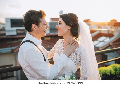 Lovely wedding couple hugs on a sunny roof