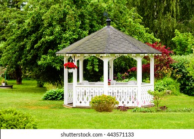 Lovely white gazebo with red flowers hanging from a basket. Trees and shrubs in the background. Fine garden with green grass.