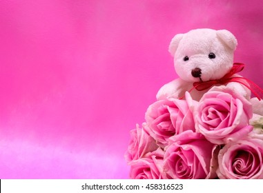 Lovely white teddy bear with beautiful pink roses bouquet on pink background.