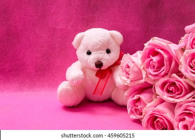 Lovely white teddy bear with beautiful pink roses on pink background