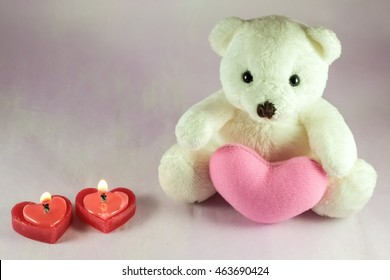 Lovely white teddy bear decorated with pink heart, heart shape candles.