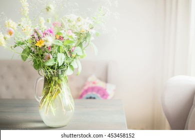 Lovely wild flowers bunch in glass vase on table in light living room , Home   decoration and interior.