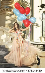 Lovely woman in beautiful dress with a lot of colorful balloons