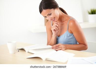 Lovely woman in blue blouse reading a book on her desk at indoor