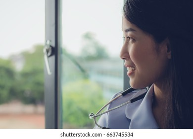 a lovely  woman in the doctor uniform looking out of the window with happiness