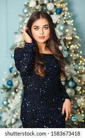 Lovely woman in evening dress over christmas tree background. Christmas holidays, celebration and sales. Festive makeup and haistyle. Fashion shiny dress. Seductive luxury model girl