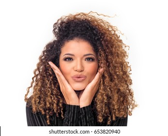 Lovely woman with gorgeous curly hair giving a kiss