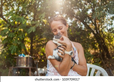 Lovely woman holding baby cat. Raylight through trees. Natural landscape