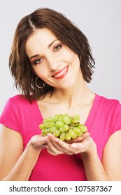 Lovely woman holding a bunch of grapes