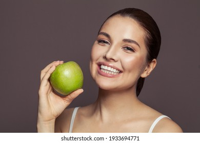 Lovely woman holding green apple and smiling on brown background