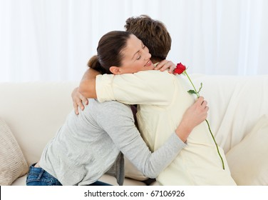 Lovely woman hugging his boyfriend after receiving a flower in the living room