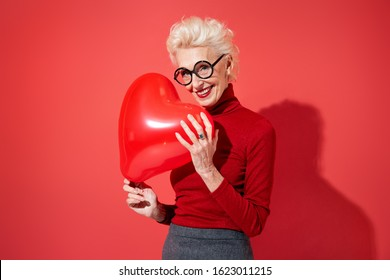 Lovely woman hugs red heart shape balloon. Photo of smiling elderly woman in love on red background. Valentine's Day