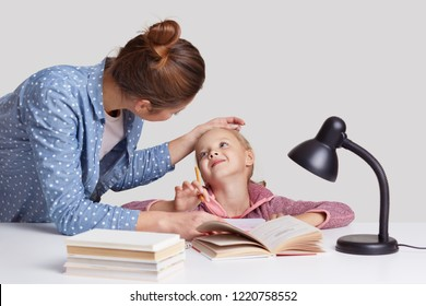Lovely woman keeps hand on daughters forehead, praises and encourgae her for studying well, pose at desktop together. Lovely little girl recieved excellent mark at school, gets praise from mum