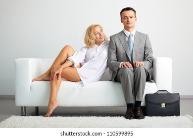 Lovely woman looking at serious businessman while both sitting on sofa