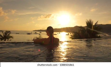 Lovely woman looks at the breathtaking tropical seaside at sunset. Unrecognizable female traveler enjoying the view of the golden sunrise from awesome oceanfront infinity pool.