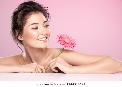 Lovely woman with pink flower and naked shoulders wearing nude make up with perfect skin at pink studio background.