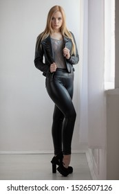 Lovely woman posing in studio dressed in black leggings and a leather jacket