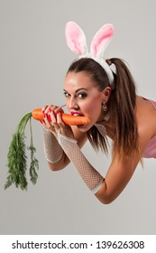 Lovely woman in rabbit costume with carrots