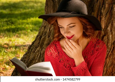 lovely woman reading a book in the autumn Park sitting on the grass