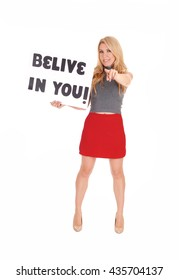 """A lovely woman in a red skirt and gray sweater standing with asign """"believe in you"""", pointing her finger, isolated for white background."""