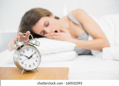 Lovely woman turning off the alarm clock lying on her bed with eyes closed