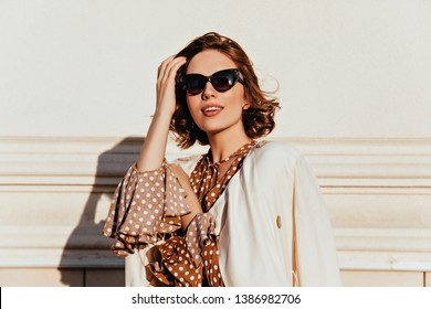 Lovely woman in vintage outfit expressing interest. Outdoor shot of glamorous happy girl in sunglasses.