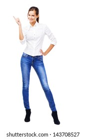 Lovely woman in white shirt and blue jeans pointing at copyspace, isolated on white background