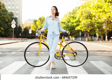 Lovely woman with a yellow bicycle on the road