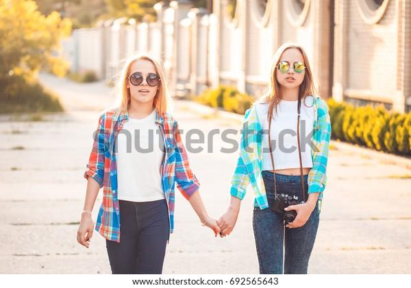 Lovely women are strolling along the street.