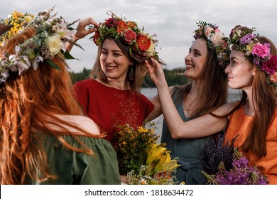 Lovely women's in flower wreaths in nature. Ancient pagan origin celebration concept. Summer solstice day. Mid summer.