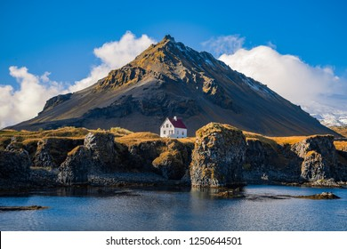 Lovely wooden houses and majestic mountains by the sea in the town of Alna Stapi, Iceland