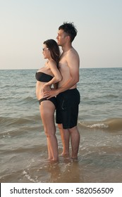 Lovely young adult couple standing on the beach .