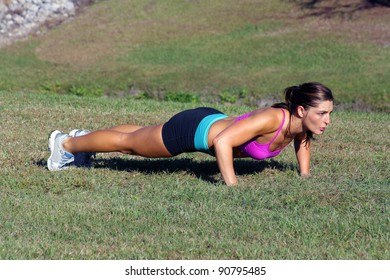 A lovely young athlete does pushups outdoors.  Generous copyspace.