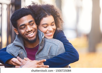 Lovely young black couple cuddling while date in autumn park, copy space