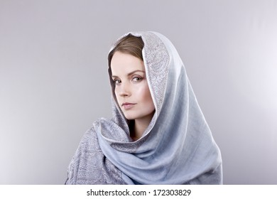 lovely young blonde in a pale blue scarf on her head on gray background