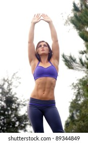 A lovely young brunette athlete stretches upward outdoors, displaying her remarkable abs.