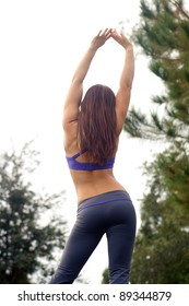 A lovely young brunette athlete stretches upward outdoors, facing away from the camera.