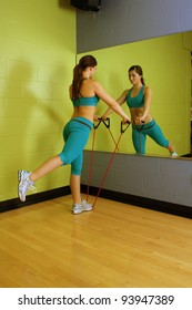 A lovely young brunette with exceptional muscle tone works out with resistance bands in front of a mirror.