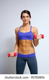 A lovely young brunette with extraordinary abdominal musculature works out with hand weights.