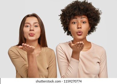Lovely young Caucasian and African American women blow air kiss at camera, express love to other people, say goodbye on distance, dressed in casual outfit, pose together against white background