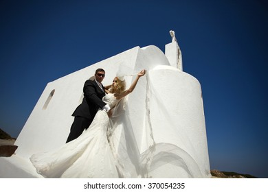 The lovely young couple beautiful woman from handsome man relating to the beautiful Greek landscape and santorini