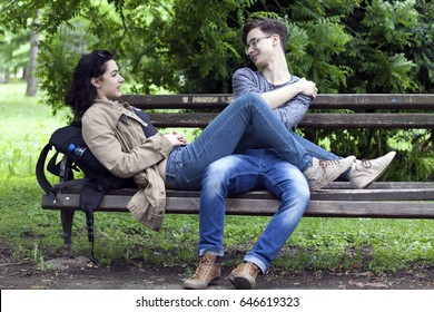 Lovely young couple, boy and girl talking in the park, enjoy and have great fun