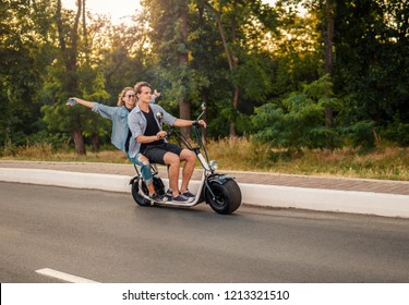 Lovely young couple driving electric bike during summer Modern city life and transportation