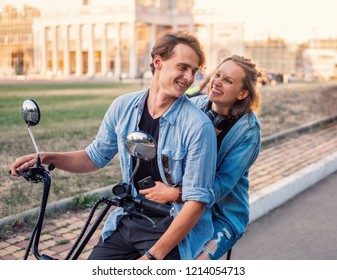 Lovely young couple driving electric bike during summer. Modern city dating and transportation
