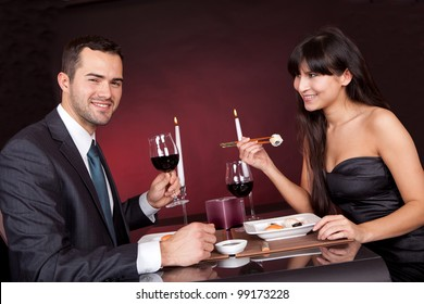 Lovely young couple eating sushi in restaurant