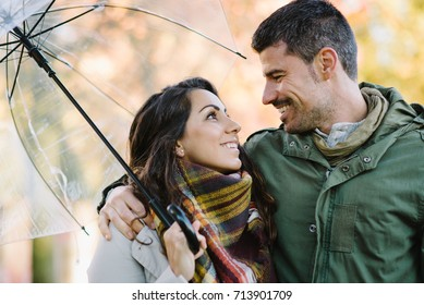 Lovely young couple flirting in autumn at the park. Romantic man and woman in love.