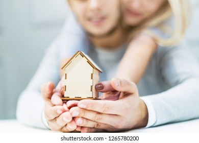 Lovely young couple holding a house layout on their outstretched hands. The concept of buying a new apartment.