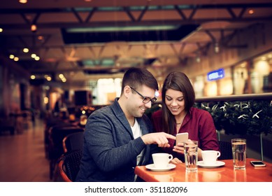 Lovely young couple looking at smart phone at cafe in trade center. Copy space for your text. Shallow depth of field. Very useful photo for processing with one click on edit image.