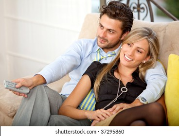 Lovely young couple relaxing watching tv and smiling